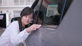 Autoverkoopcentrum, gelukkige kopers vrouwelijke Aziatische etnisch met plezier die nieuwe auto strijken die zacht bij het handel stock footage