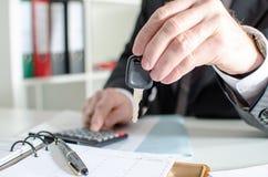 Autoverkoper die een sleutel houden en een prijs berekenen Stock Afbeeldingen