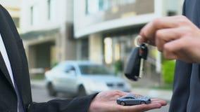 Autoverkoper die sleutels geven aan nieuwe eigenaar, mannelijke tonende stuk speelgoed auto aan persoon, overeenkomst stock video