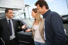 Autoverkoper die sleutels overhandigen aan cliënten stock afbeelding
