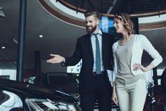 Autoverkoper Showing Car aan Vrouw in Toonzaal stock afbeeldingen