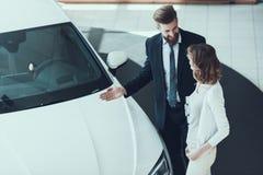 Autoverkoper Showing Car aan Vrouw in Toonzaal royalty-vrije stock afbeelding