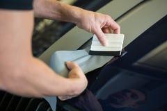 Autoverpackung, die Folie mit einer Gummiwalze geraderichtet Lizenzfreie Stockfotografie