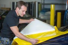 Autoverpackung, die Folie vorbereitet, um ein Fahrzeug einzuwickeln Lizenzfreies Stockfoto