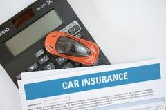 Autoversicherungskonzept mit Autoversicherungsform, Spielzeugauto und Draufsicht des Taschenrechners lizenzfreie stockbilder