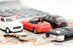 Autoversicherungskonzept mit Spielzeugautos, Autoschlüssel, Münzen und Rechnungen Stockfotos