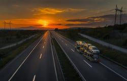 Autovervoerdersvrachtwagen bij Zonsondergang Stock Foto