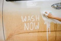Autowas met modderplonsen van regenachtig seizoen voor met de tekstbericht van de wasauto Stock Afbeelding