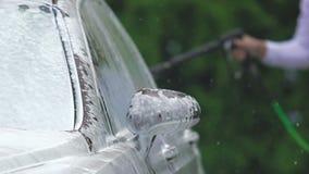 Autowasserette bedrijfswerknemer die schuimende auto schoonmaken, die duidelijk water op cabine bestrooien stock video