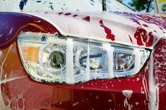 Autowasserette met een niet-contactschuim, koplamp met een dik schuimclose-up royalty-vrije stock foto's