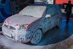 Autowasserettezelfbediening zonder contact Jonge mens die zijn auto wassen stock fotografie