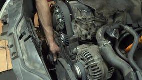 Autowerktuigkundige die een rubbertoestelriem veranderen stock footage