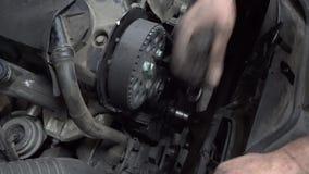 Autowerktuigkundige die een rubbertoestelriem veranderen stock videobeelden