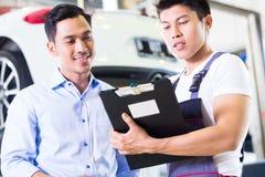 Autowerktuigkundige en klant in Aziatische autoworkshop Stock Afbeeldingen