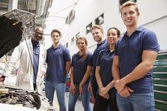 Autowerktuigkundige en leerlingen in een garage die aan camera kijken royalty-vrije stock foto