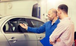 Autowerktuigkundige met klembord en mens bij autowinkel royalty-vrije stock afbeeldingen