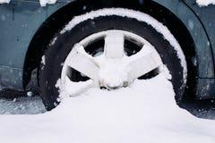 Autowiel met de winterbanden in de sneeuw Wiel in een sneeuwbank wordt geplakt die Sneeuwafwijkingen op weg, slecht weer stock afbeelding