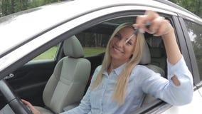Autozaken, autoverkoop, consumentisme en mensenconcept - de gelukkige vrouw die autosleutel van handelaar in auto nemen toont of  stock video