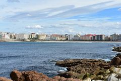 La Coruna from promenade. Rocks, blue water with foam, beach, promenade and bay. Autumn background. Galicia, Spain. stock images