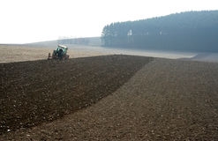 Autum moods. Wide open landscape with ploughed field with a farm tractor in the middle waiting for winter Royalty Free Stock Images