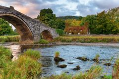 Autum Sunrise at Llanrwst Bridge. Autumn sunrise over the Pont Fawr bridge crossing the river Conwy at Llanrwst in North Wales royalty free stock photo