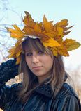 Autumn. The girl in a wreath from autumn leaves royalty free stock images