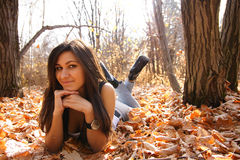 Autumn. Beautiful young woman lays on autumn leaves Stock Photography