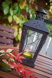 Autumn. Lantern on the table with some autumn color leaves around Stock Photo