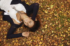 Autumn. Girl in autumn orange leaves. Outdoor royalty free stock image