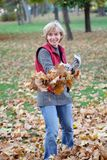 Autumn. Smiling mature woman raking leaves in a garden Royalty Free Stock Photo