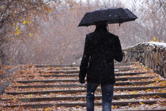 Autumn. Man with a umbrella walks upstairs fallen asleep by leaves Royalty Free Stock Photography
