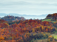 Autumn. Hill in autumn with colorful forest and church on top Royalty Free Stock Photo