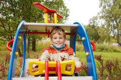 In autumn afternoon, boy plays on playground Royalty Free Stock Photos