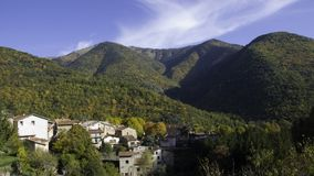Autumn in the alps. Autumn colored hills and village in the french alps Stock Photo