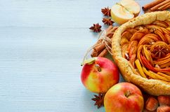 Autumn apple pie on the wooden board decorated with fresh apples, hazelnuts, spices - anise, cinnamon on the gray kitchen table. Thanksgiving tart and various stock image