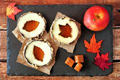 Autumn apple rounds with caramel filled centers on slate server Royalty Free Stock Image