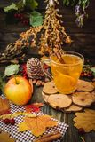 Autumn apple tea. Autumn still life with apple spice tea on the wooden background and maple leaves Stock Image
