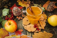 Autumn apple tea. Autumn still life with apple spice tea on the wooden background and maple leaves Royalty Free Stock Images