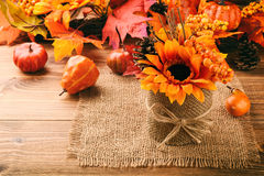 Autumn arrangement - pot with artificial sunflower, cones and leaves on wooden background. Stock Image
