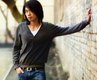 Autumn Asian man and brick wal Royalty Free Stock Images