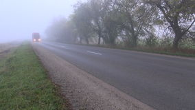 Autumn asphalt road with red truck and  fog stock video