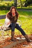 Autumn attractive woman eat apple sunset park Stock Photo