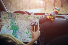 Autumn, Auto travel. Cose-up of a woman drinking take away cup coffee during the road trip in a car. The driver checks. The paper map. Woman feet in warm socks stock photo