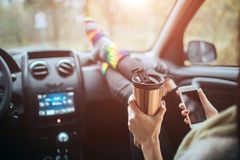 Autumn, Auto travel. Cose-up of a woman drinking take away cup coffee during the road trip in a car. Woman feet in warm. Socks on car dashboard. Drinking take stock photos