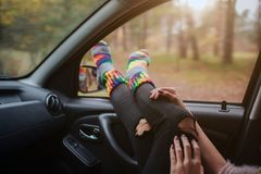 Autumn, Auto travel. Cose-up of a woman during the road trip in a car. Woman feet in warm socks on car dashboard. Autumn, Auto travel. Cose-up of a woman during stock images