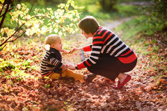 Autumn baby boy and mother  consider reading a book under a tree Royalty Free Stock Image