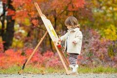 Autumn Baby Girl Drawing in het Park van Dalingsbladeren, Weinig Jong geitje het Schilderen, Kinderencreativiteit Stock Fotografie