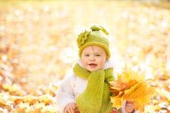 Autumn Baby, glückliches Kinderdraußen Porträt mit gelben Fall-Blättern Stockbild