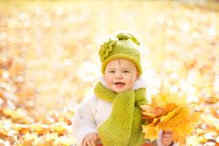Autumn Baby, retrato feliz del niño al aire libre con las hojas amarillas de la caída Imagen de archivo