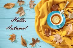 Autumn background concept - blue cup of black tea with lemon slice and honey on a yellow scarf, dried leaves and text Hello, Autum royalty free stock photography